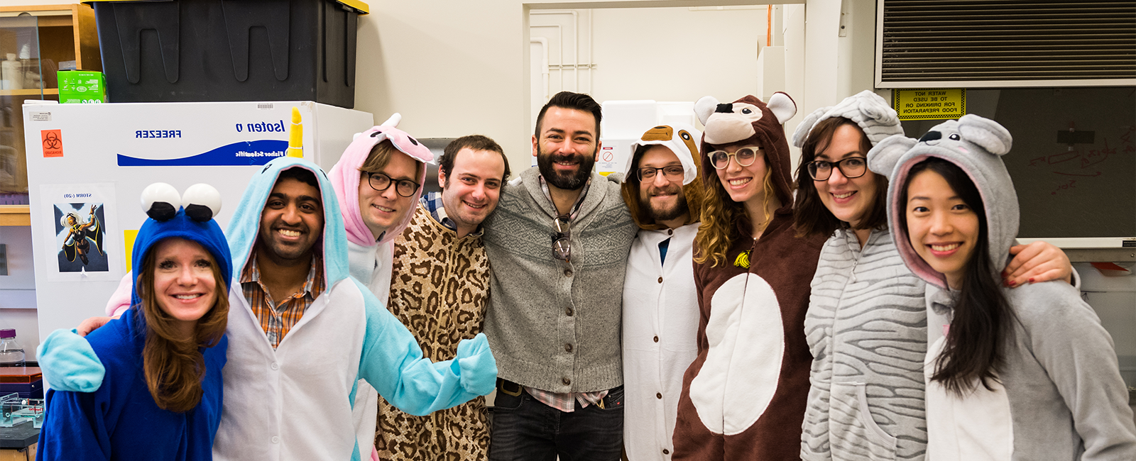 Professor Alex Shalek poses with members of his research group, who are jovially dressed in animal onesies.