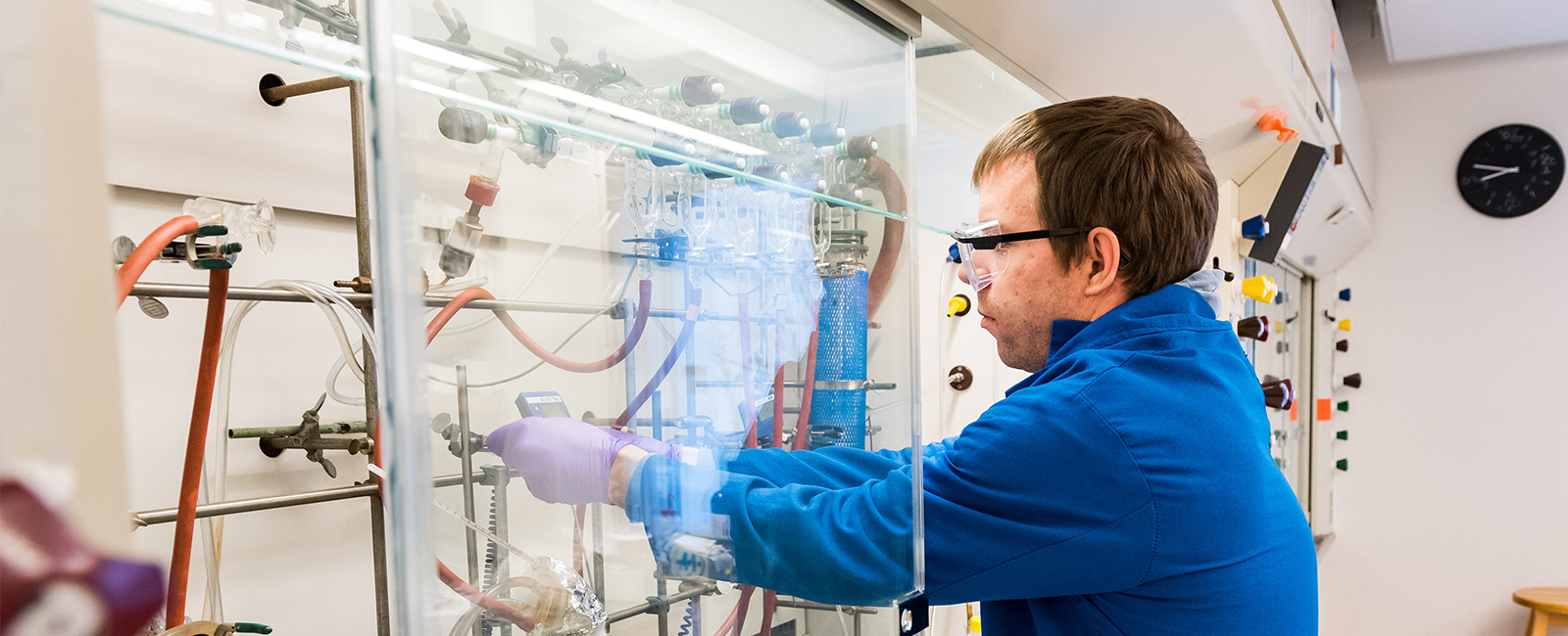 A graduate student conducts research at a fume hood.