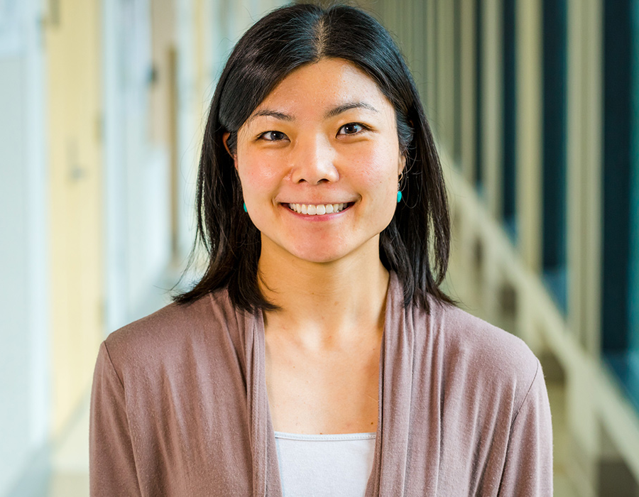 Postdoc 益子修早矢香 stands in the hallway of the Chemistry Building.