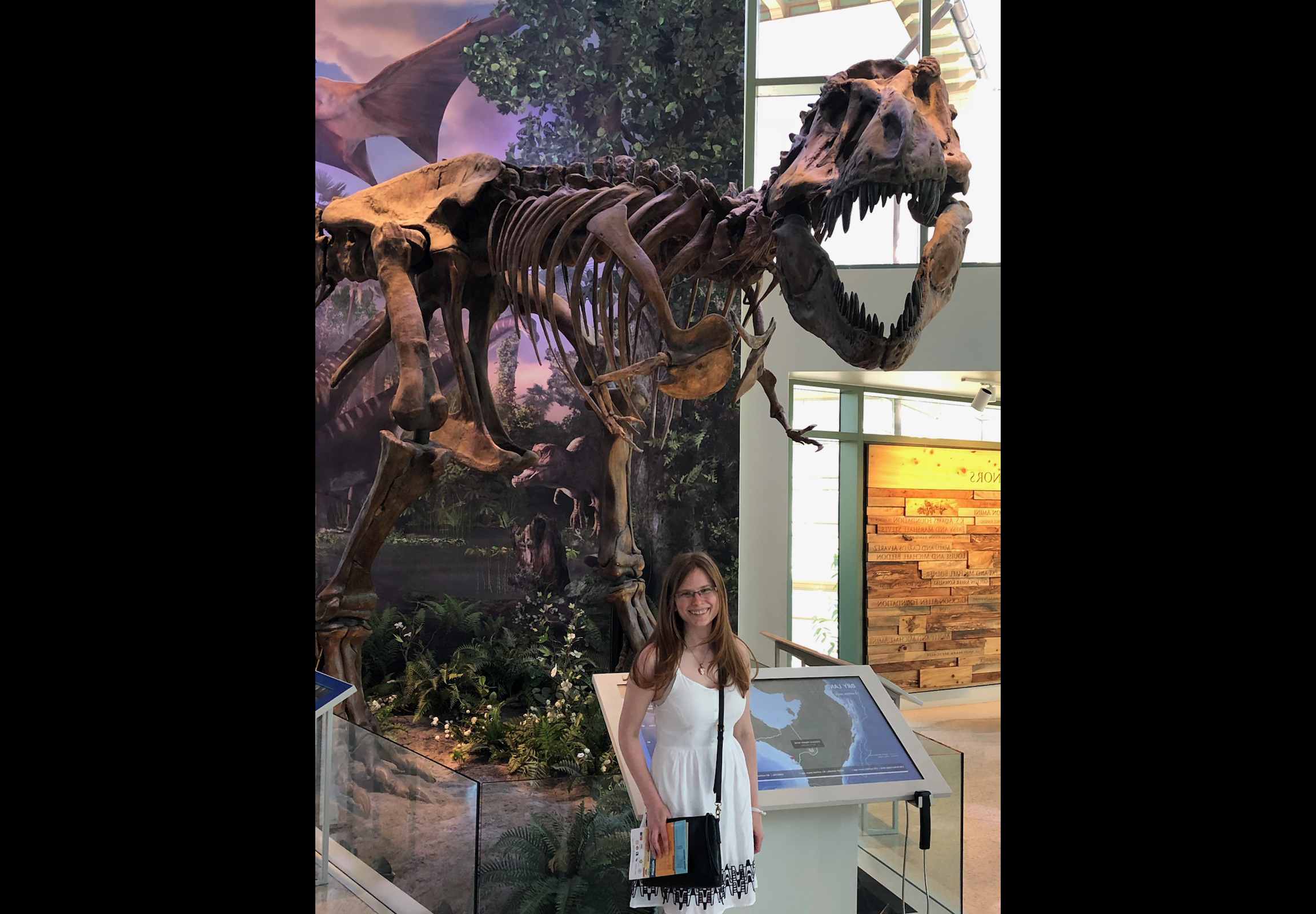 Nicole Moody poses before a T-Rex Skeleton