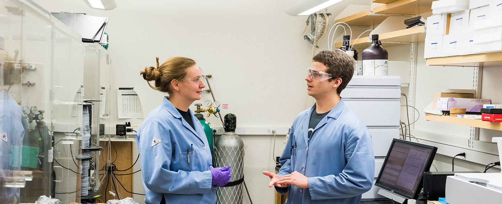 Two graduate students talk about their research in a lab.