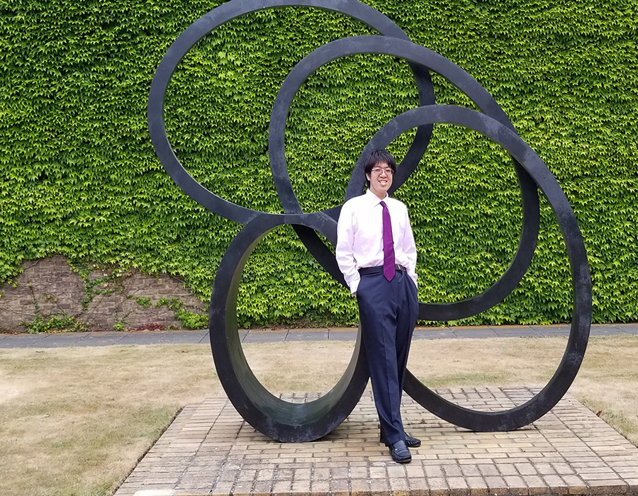Graduate Student 亨利TRAN poses outdoors in front of a sculpture.