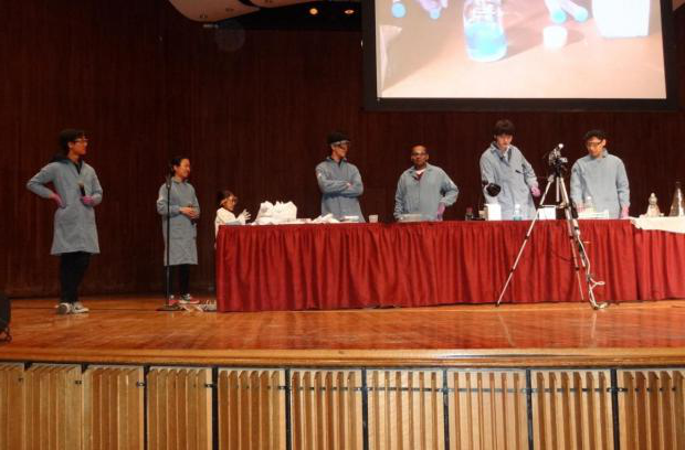 Members of Club Chem present a Chemistry Magic Show on stage before an audience.