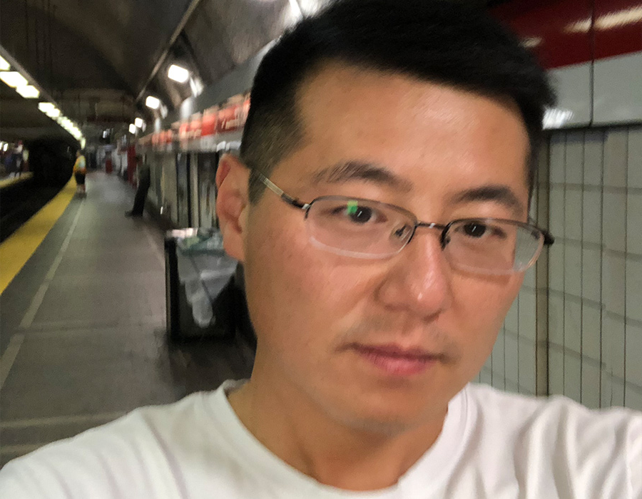 Postdoctoral researcher 温州 stands on the subway platform.