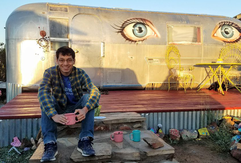 A male graduate student sits in front of an airstream trailer painted with two blue eyes.